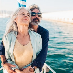 Älteres Päärchen umarmt sich auf einem Segelboot